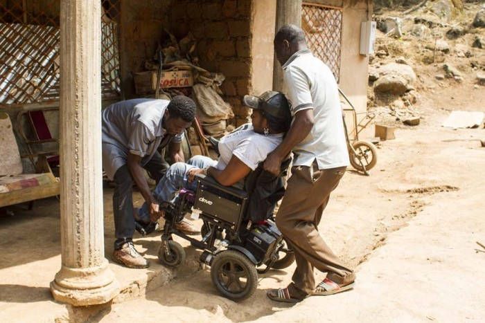 Hilda Bih enters in a building with a help of two men as the building is not wheelchair accessible.